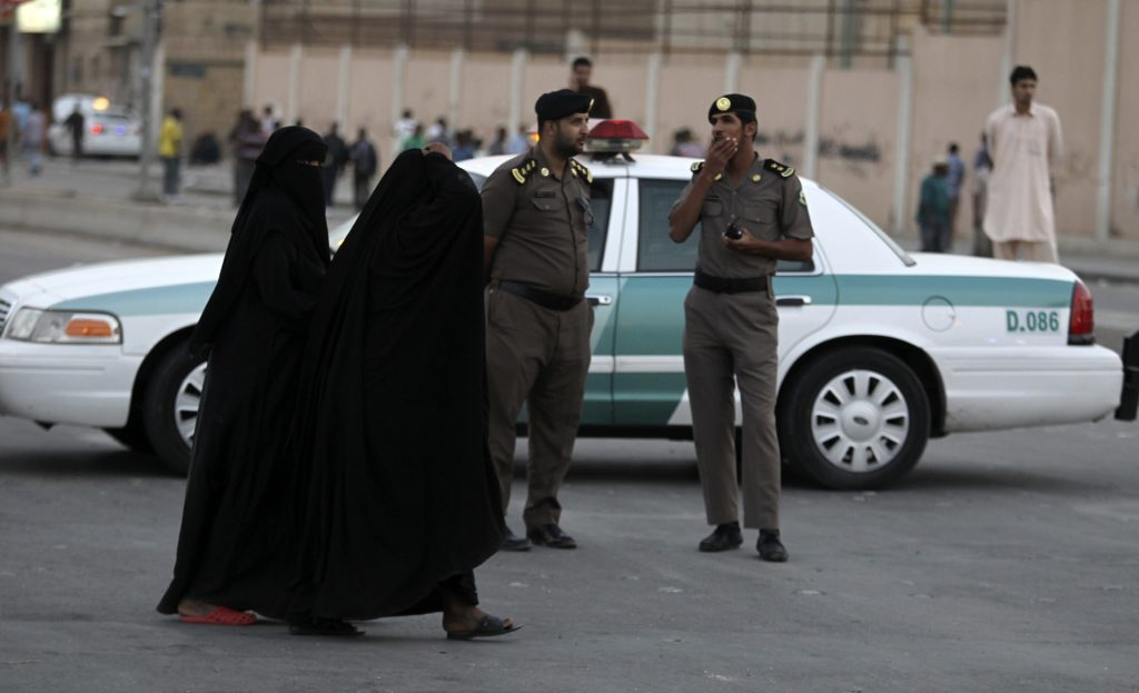 Women walk past members of Saudi security forces as they keep guard in Manfouha, southern Riyadh, November 14, 2013. A Sudanese man was killed in a second flare of clashes since Saturday between Saudi riot police, citizens and foreign workers in Riyadh amid a clampdown on visas, state media said late on Wednesday. The report on the official Saudi Press Agency, which cited a Riyadh police spokesman, gave no further details about the dead man, but said the clashes had started as a dispute between Saudis and foreigners earlier in the day. REUTERS/Faisal Al Nasser (SAUDI ARABIA - Tags: CIVIL UNREST SOCIETY IMMIGRATION)